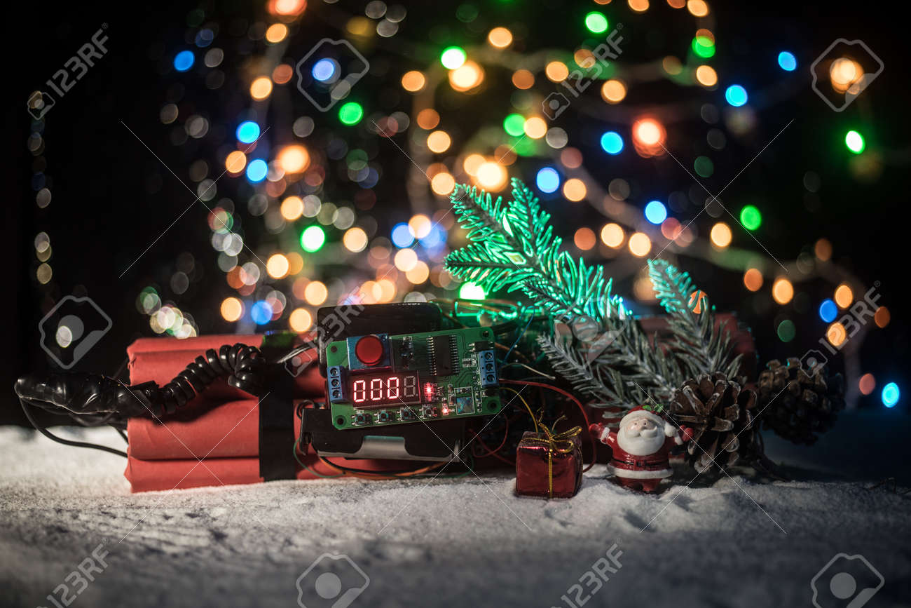 Christmas and New Year funny concept. Time bomb (dynamite) on snow with holiday decor and santa. Timer counting down and New Year is coming. Selective focus - 158586253