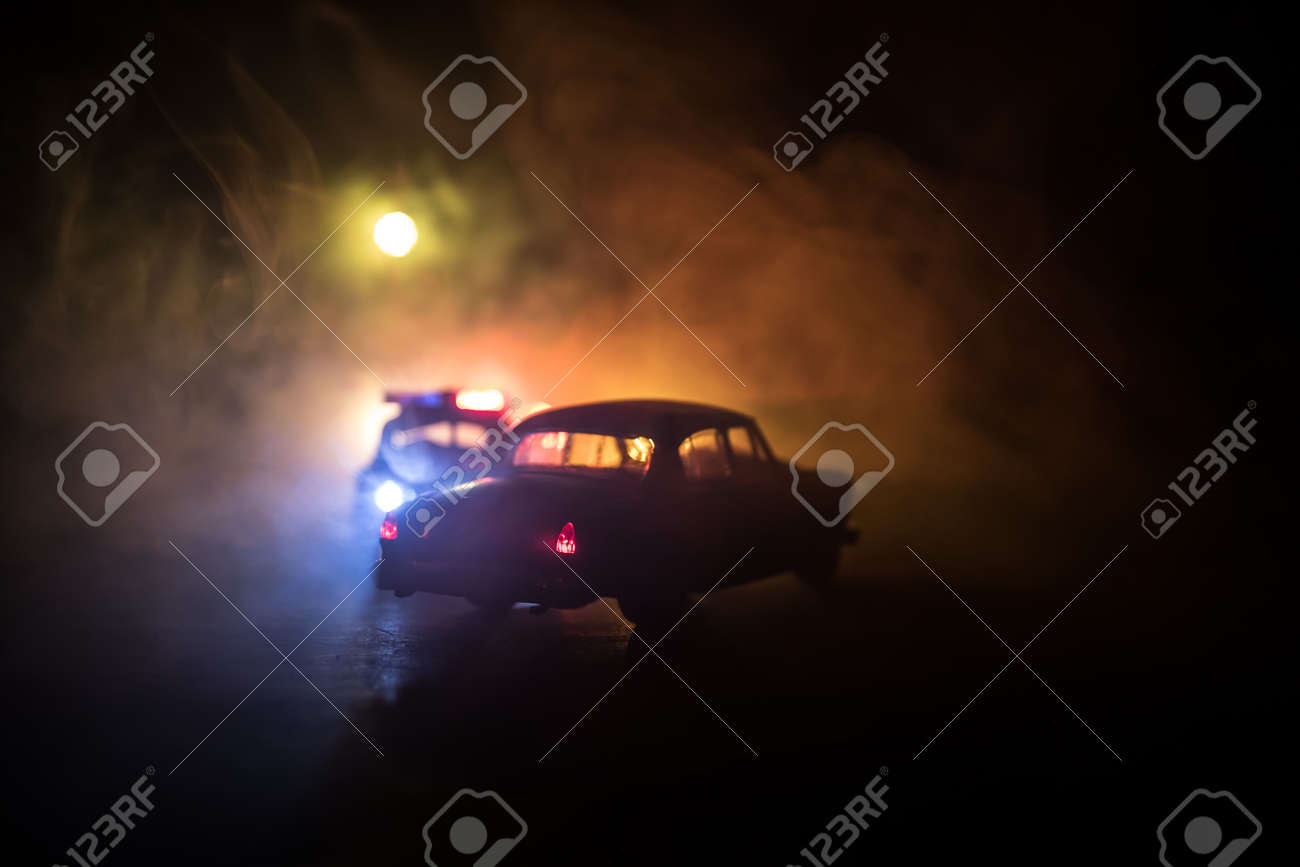 Police car chasing a car at night with fog background. 911 Emergency response police car speeding to scene of crime. Selective focus - 168337764