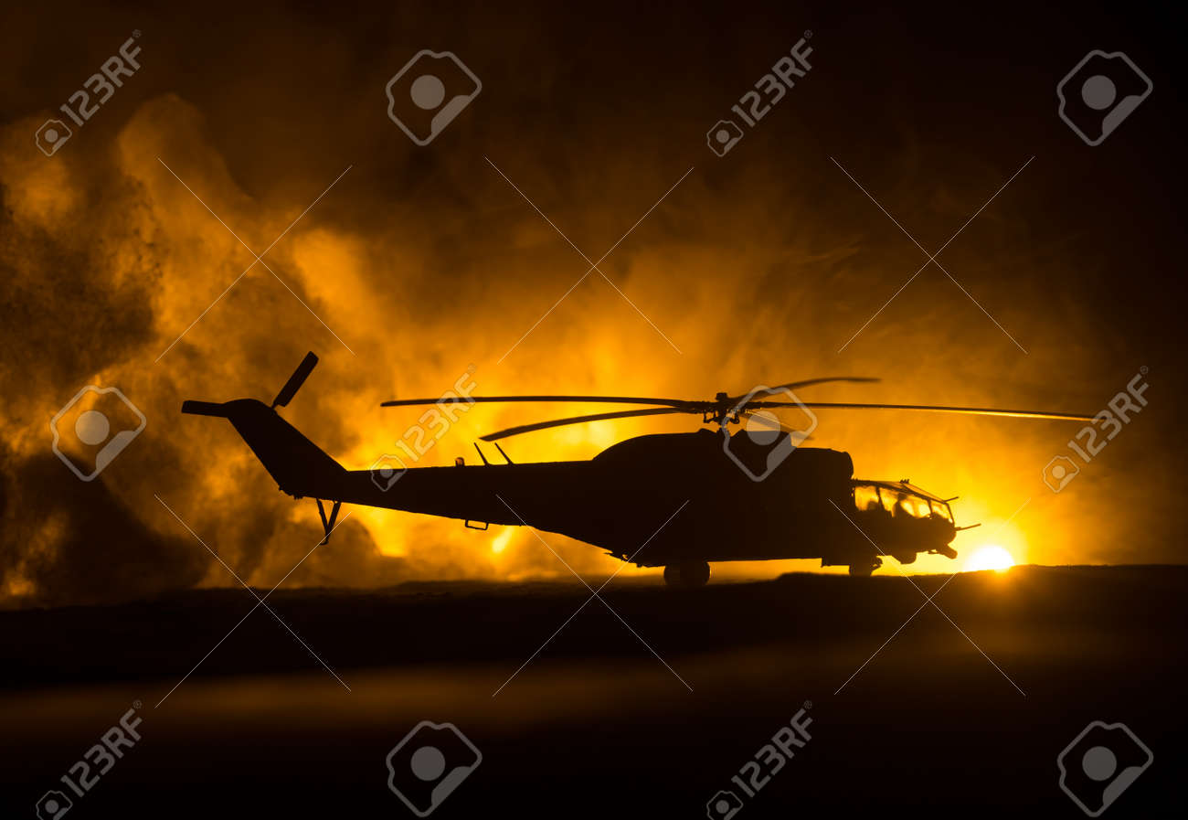 Silhouette of military helicopter ready to fly from conflict zone. Decorated night footage with helicopter starting in desert with foggy toned backlit. Selective focus. War concept - 168338069
