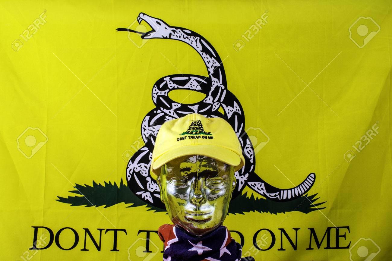 glass head wearing yellow baseball hat and gadsden flag stock photo
