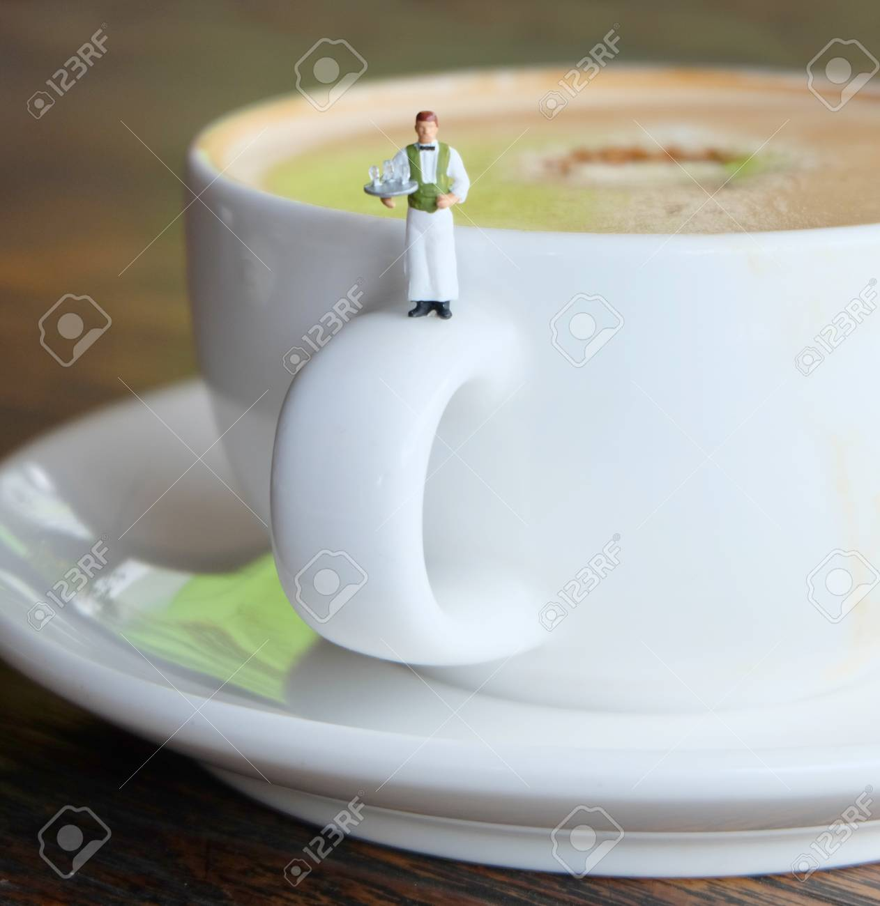 Miniature Waiter Serving a Cup of Hot Coffee Stock Photo - 82873267