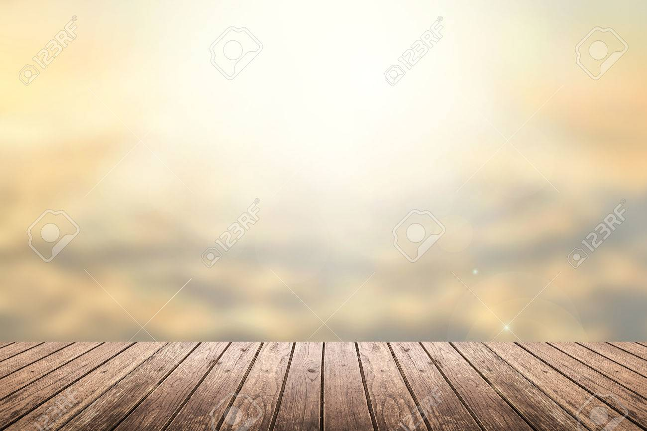 Brown wooden floor with abstract blurred background in sunset sky tone color and sunlight on top. use for backdrop or web design - 44975245