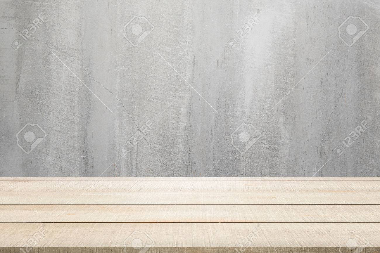 Beige wood table top panel on grunge gray concrete wall texture background with top light