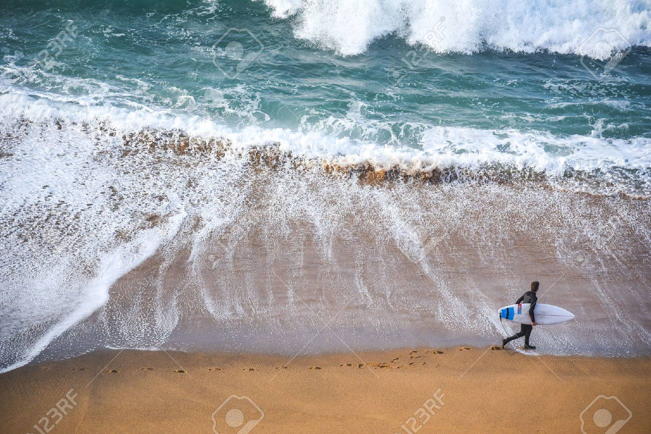 surfer man on the beach with turquoise-white water wave in the sea from top view at Bells beach, Torquay, Australia. - 62016418