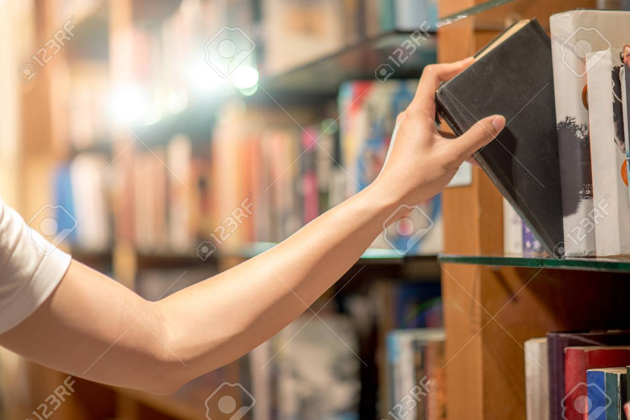 Right hand of young man picking a book from bookshelf in library, reading and learning concepts - 78203440