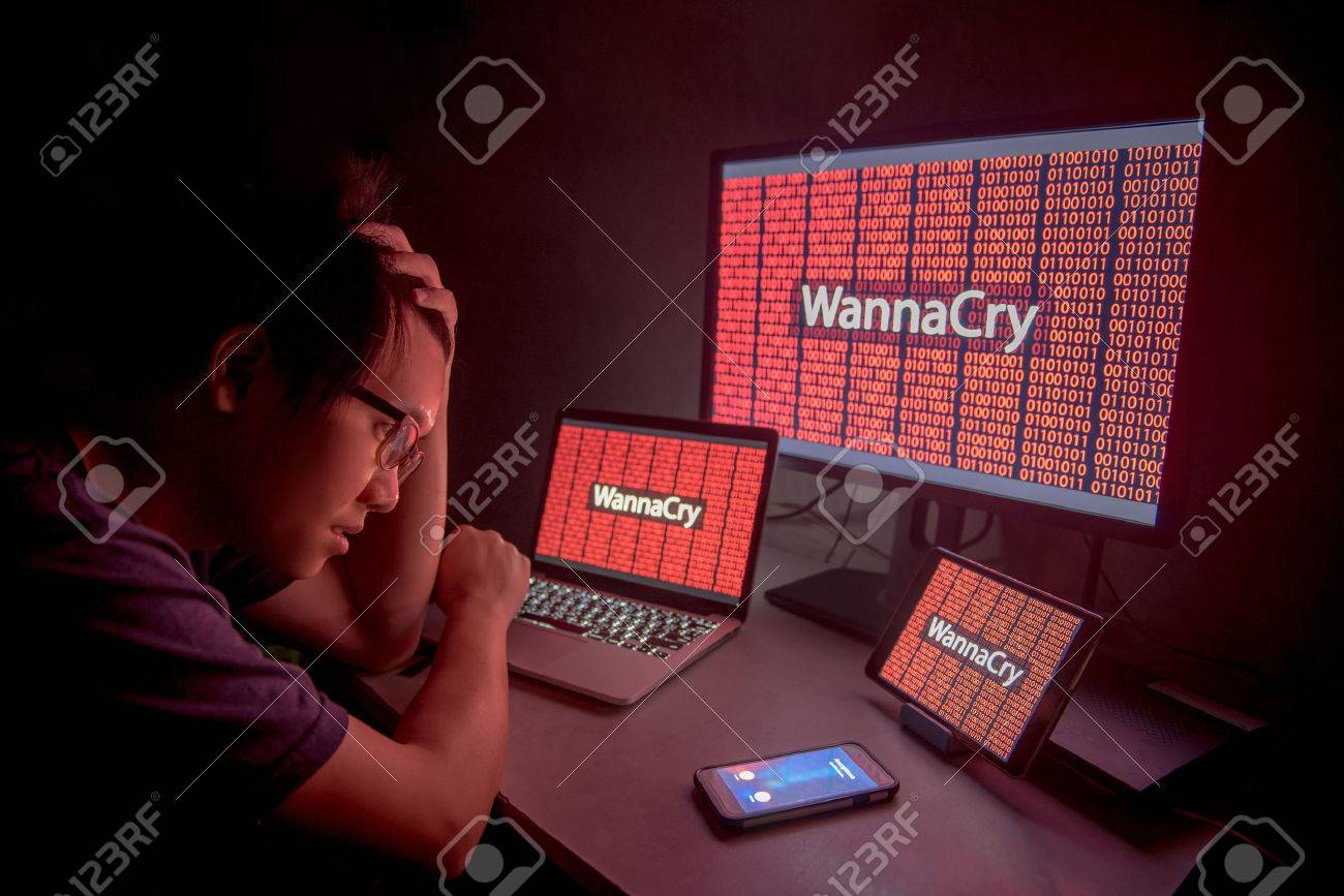 WannaCry ransomware attack on desktop screen, notebook and smartphone, internet cyber attack with Anonymous calling on smart phone to get the ransoms payment to decrypt the code - 78351153