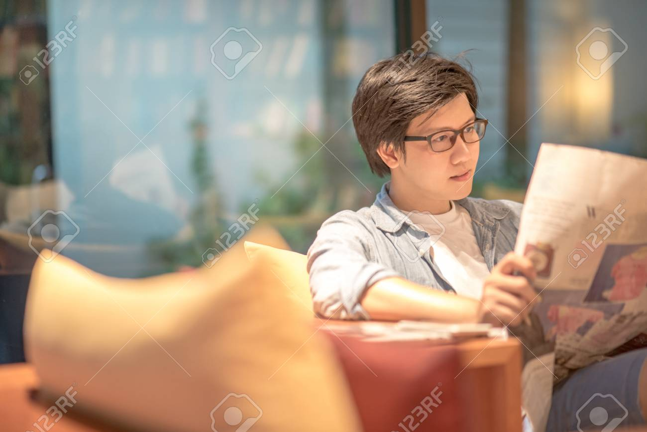 Young Asian casual businessman reading newspaper on sofa in living room, update daily information from printing media - 80765372