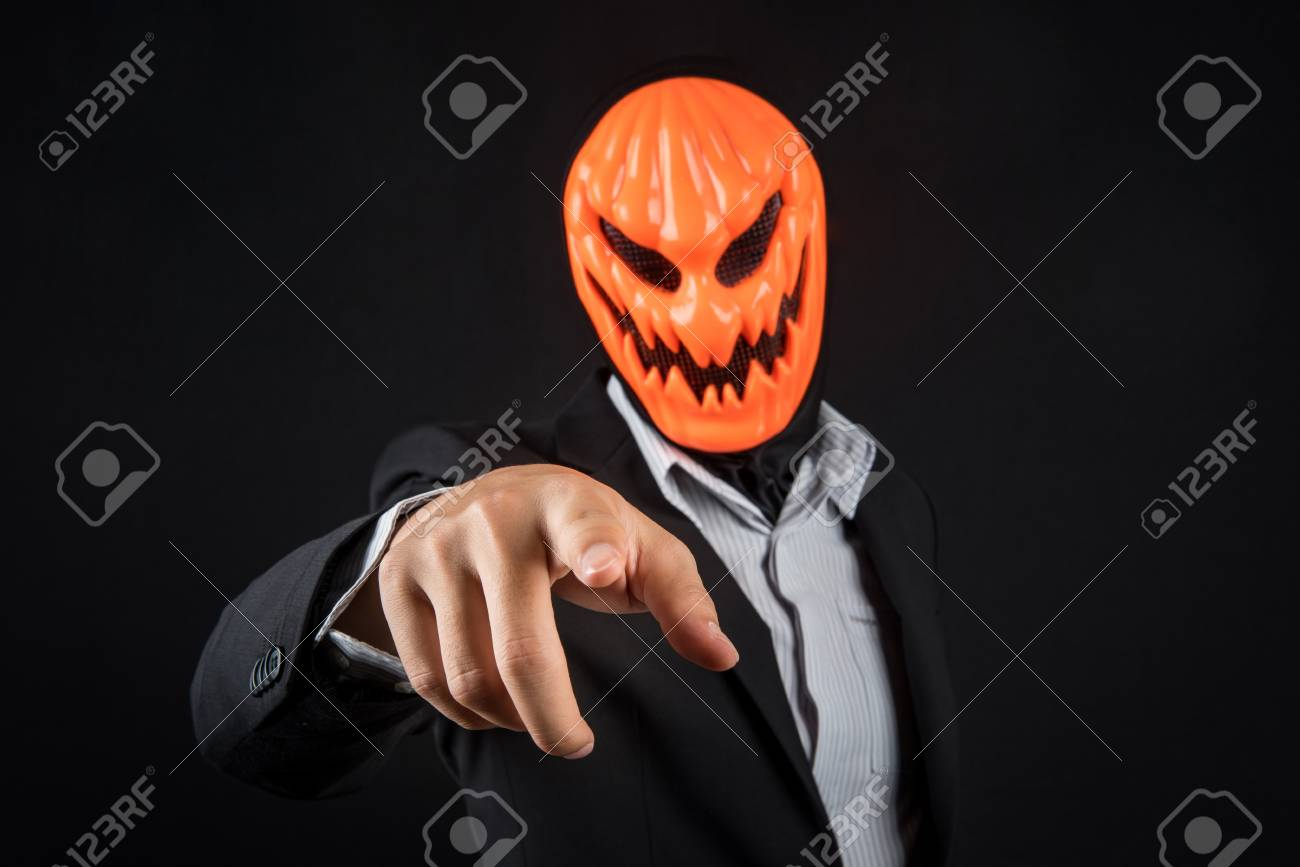 ... Halloween night costume concept. Mystery business man with orange pumpkin evil mask and working suit pointing hand on black background & Mystery Business Man With Orange Pumpkin Evil Mask And Working ...