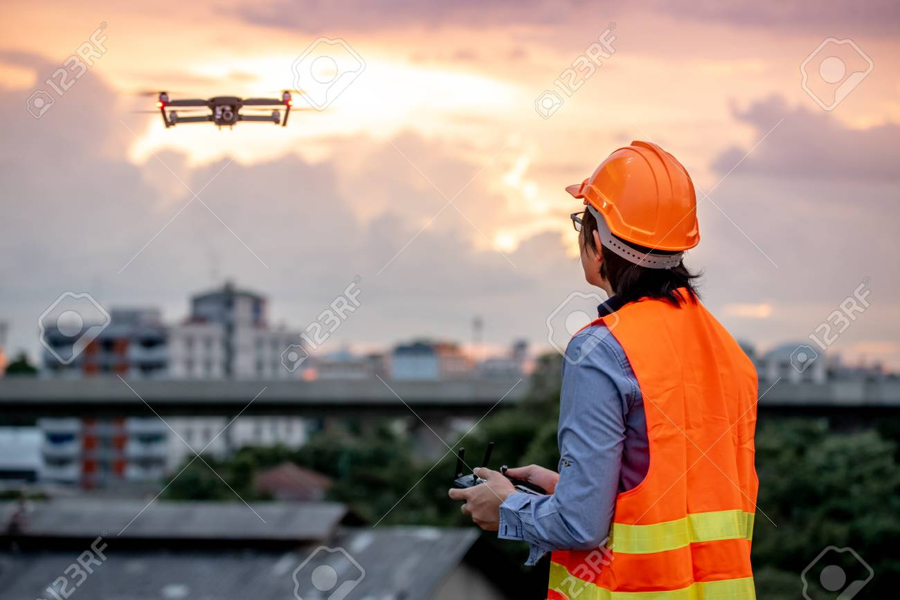 Young Asian engineer flying drone over construction site during