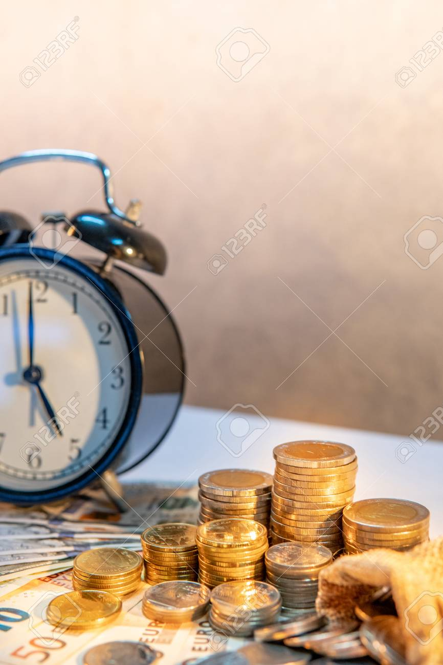 Stock Photo   Table Clock And Gold Coin Stack On The Table With  International Banknotes Currency. Time Investment And Passing Time.