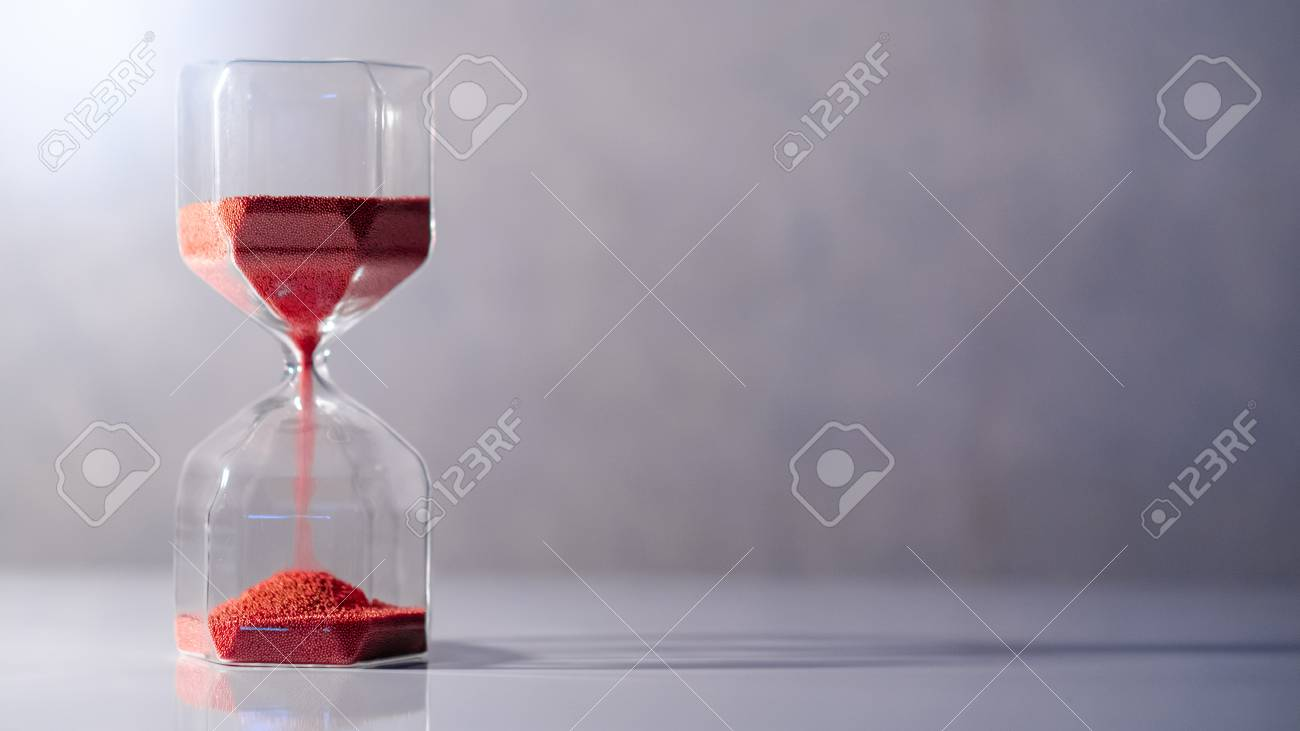 Red sand running through the shape of modern hourglass on white table.Time passing and running out of time. Urgency countdown timer for business deadline concept with copy space - 107254409