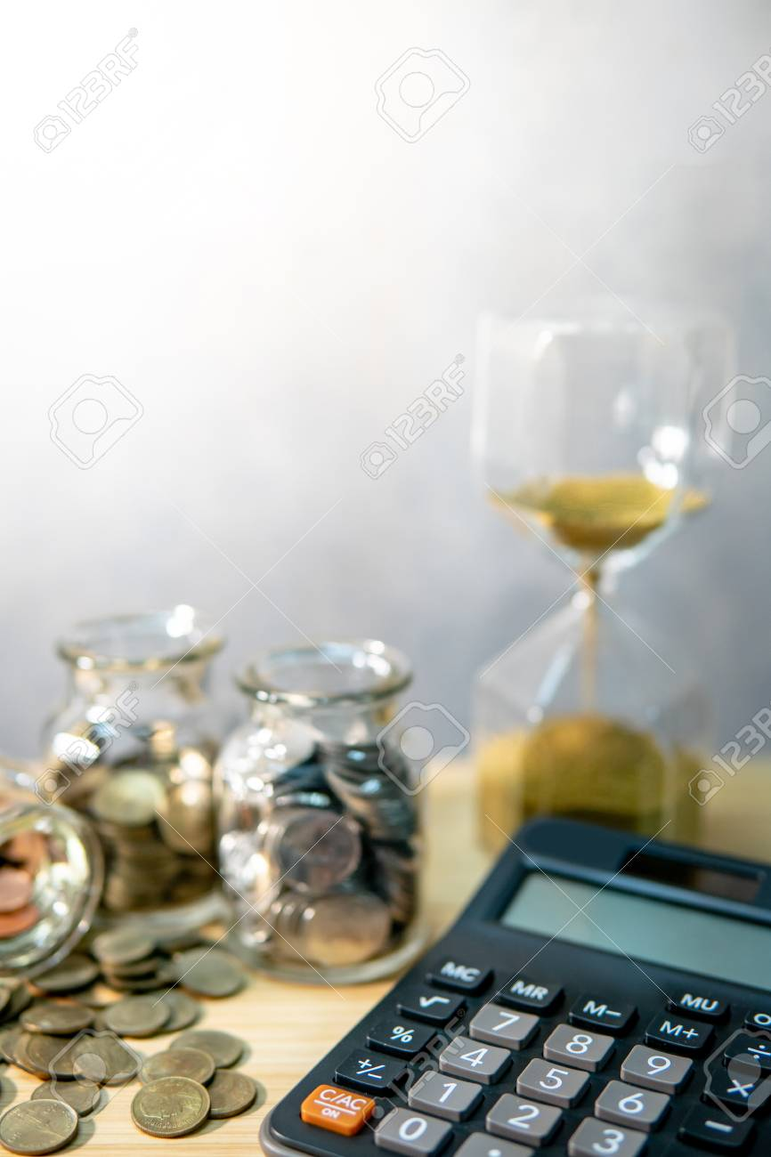 calculator with coin in currency glass jar and hourglass on wooden