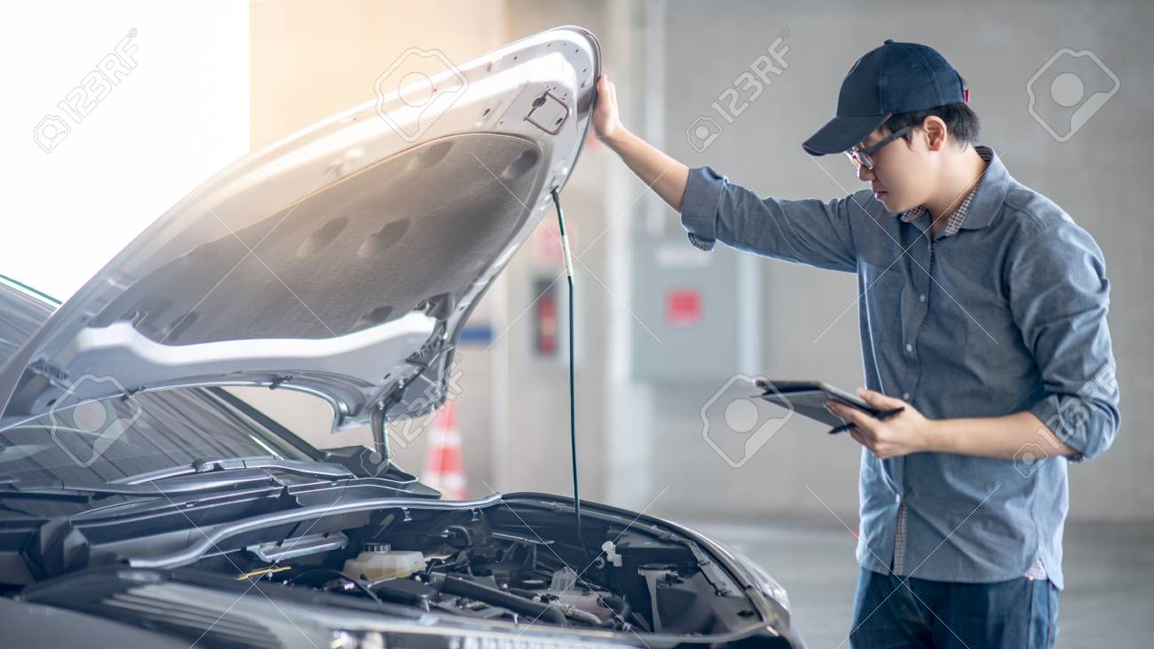 Asian auto mechanic holding digital tablet checking car engine under the hood in auto service garage. Mechanical maintenance engineer working in automotive industry. Automobile servicing and repair - 110927741