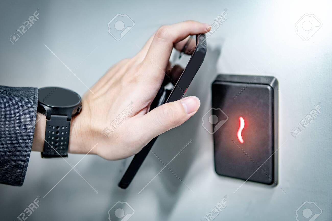 Male hand using smartphone for sensor scanning. Infrared sensor technology for automatic door access and security. - 127828857