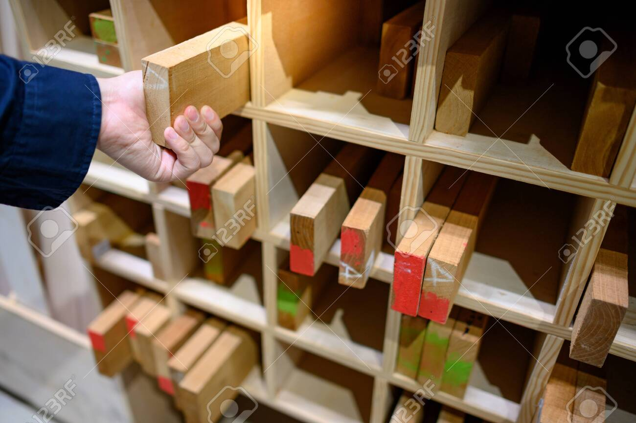 Male hand choosing wood lumber from wooden shelf in factory. Wood industry concept - 140494869