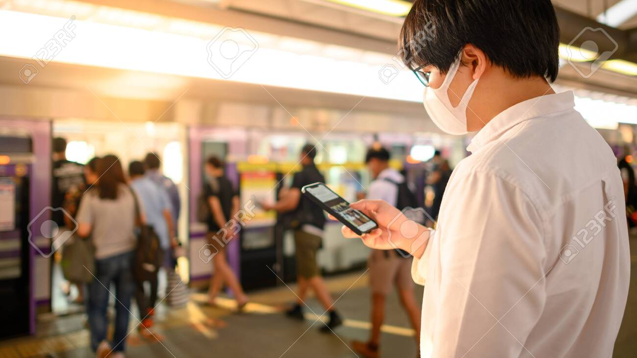 Asian man wearing surgical face mask using smartphone at skytrain station platform. coronavirus (COVID-19) outbreak prevention in public transportation. Health awareness for pandemic protection - 143782592