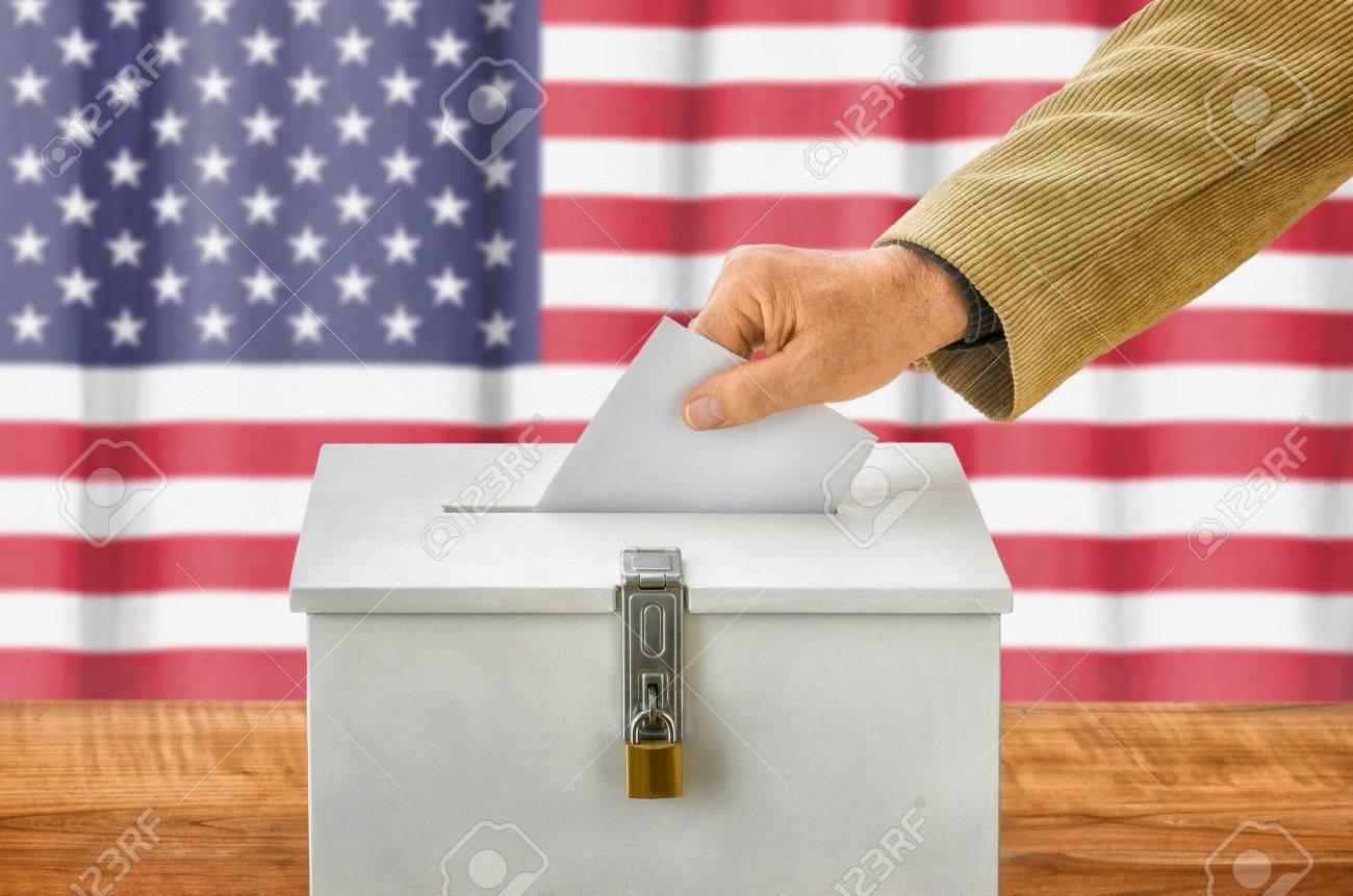 Man putting a ballot into a voting box - USA - 47062864