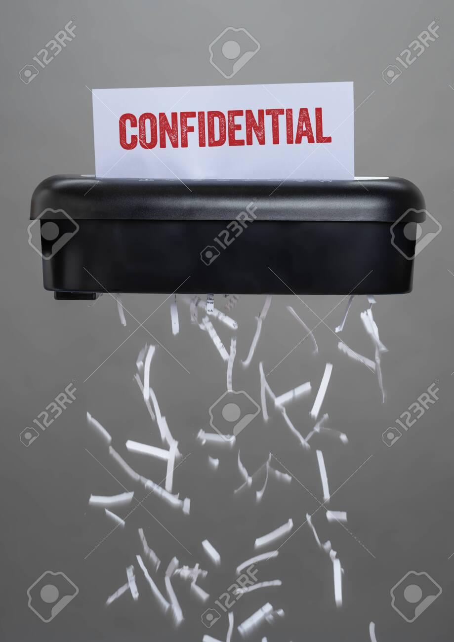 A shredder destroying a document - Confidential - 121532475