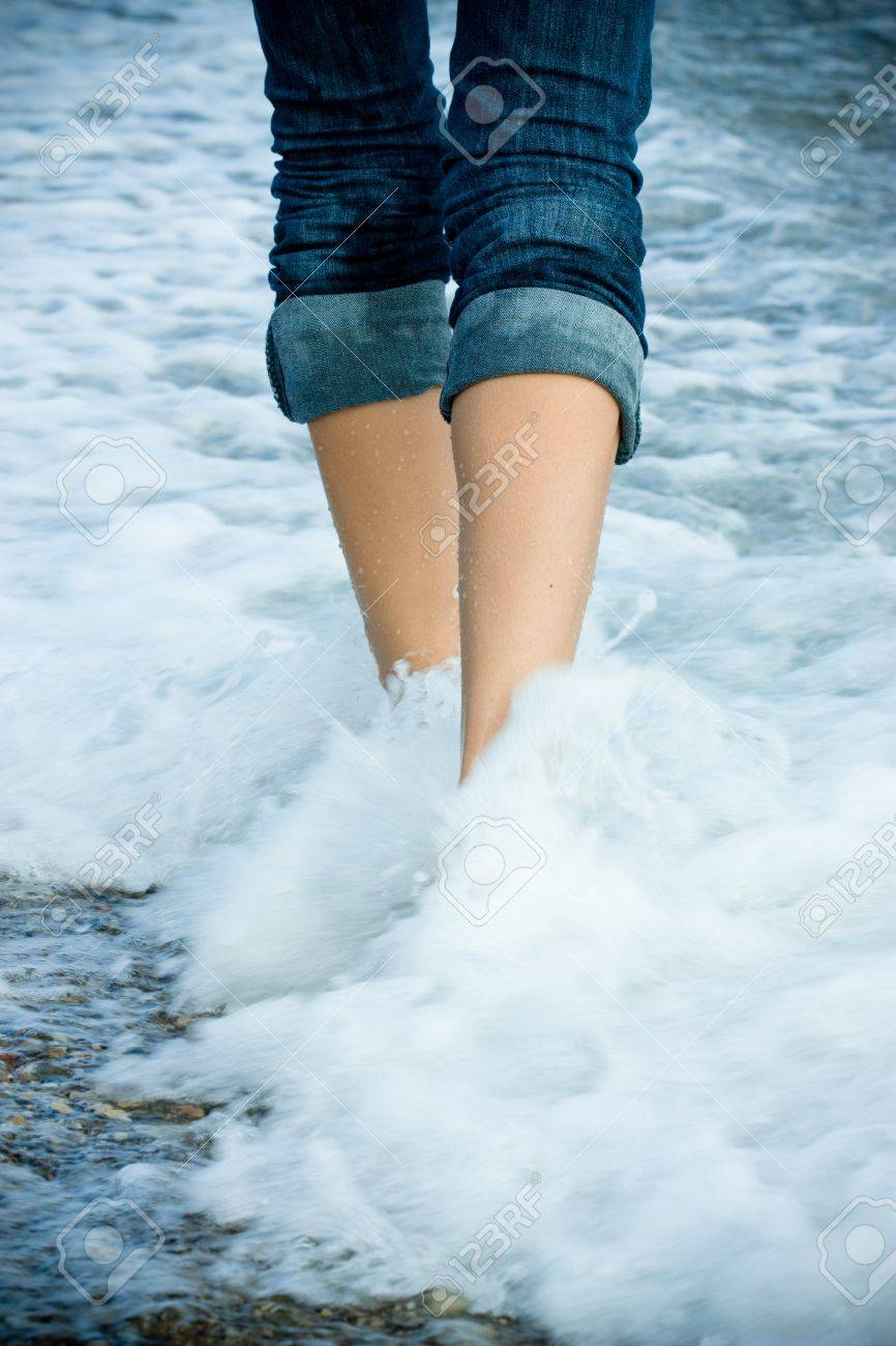 Legs of a young woman walking along the seacoast Stock Photo - 10345903