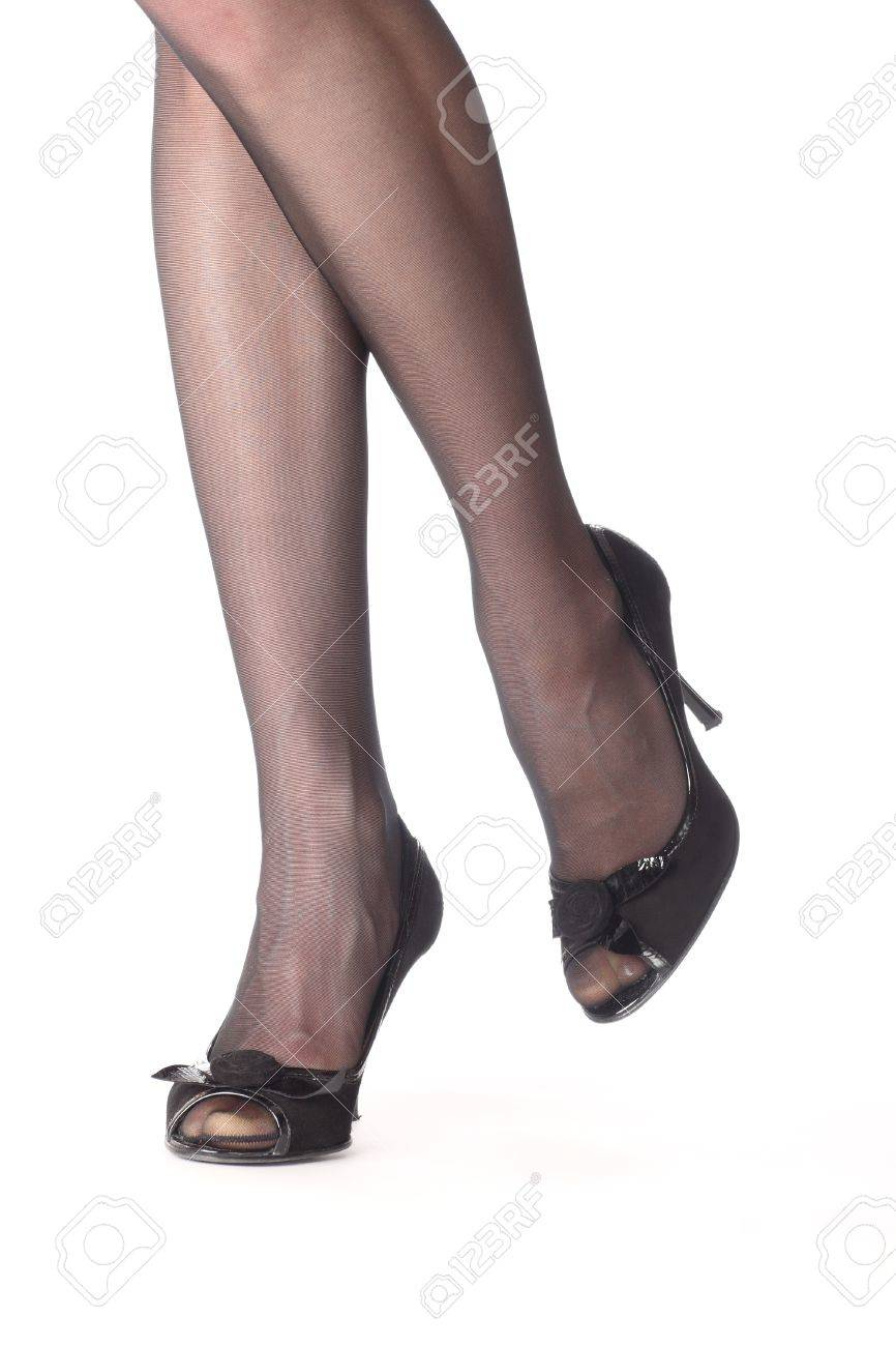 Close-up of young woman�s legs in high-heeled black shoes isolated on white Stock Photo - 10816639