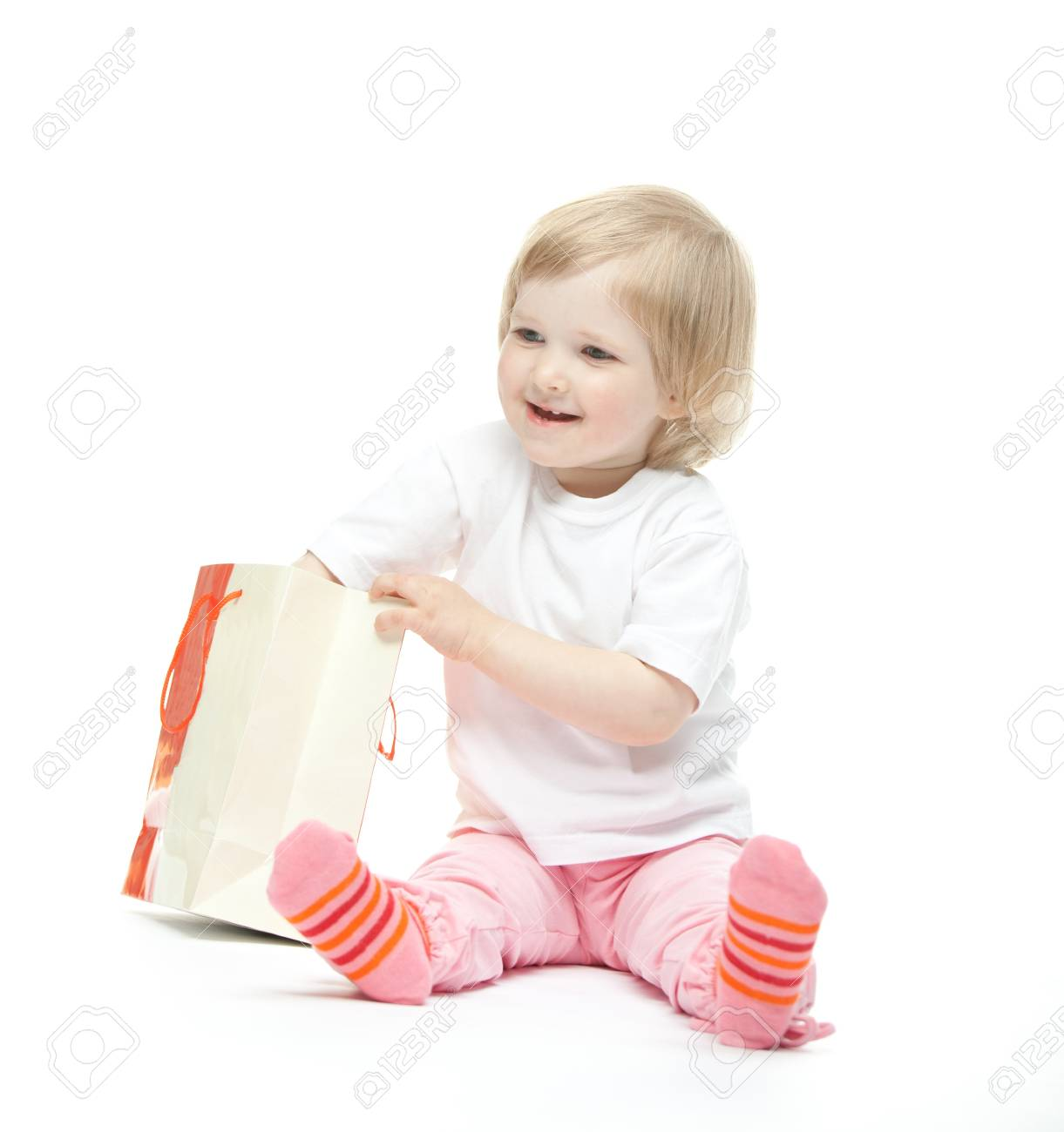 The baby girl finds a present. White background Stock Photo - 11174310