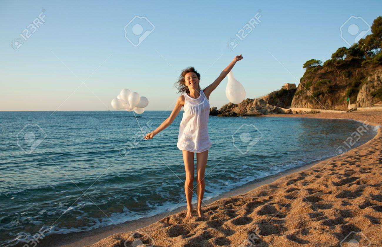 Happy smiling brunette girl with white balloons on sunny beach; attractive young woman enjoying summer vacation at the sea Stock Photo - 12907205