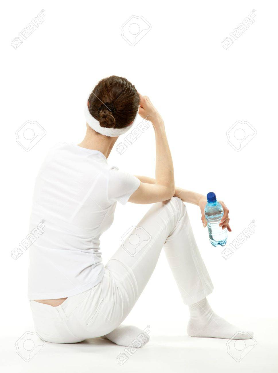 Young woman relaxing after sport; slender young woman sitting on the floor holding bottle of drinking water, rear view, white background Stock Photo - 13193054
