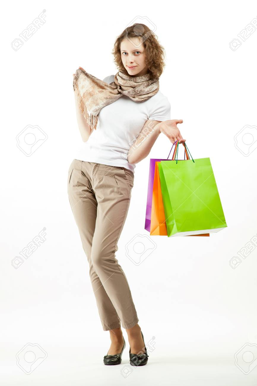 Shopping concept: happy beautiful young woman holding multicolored paper bags; full length portrait on white background Stock Photo - 13532936