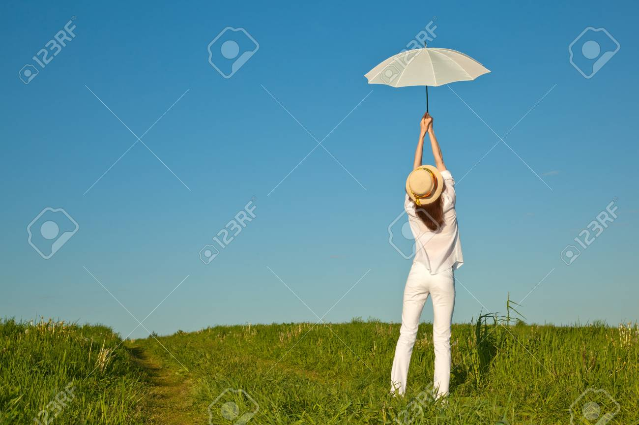 Beautiful girl with white umbrella in summer meadow Stock Photo - 14001376