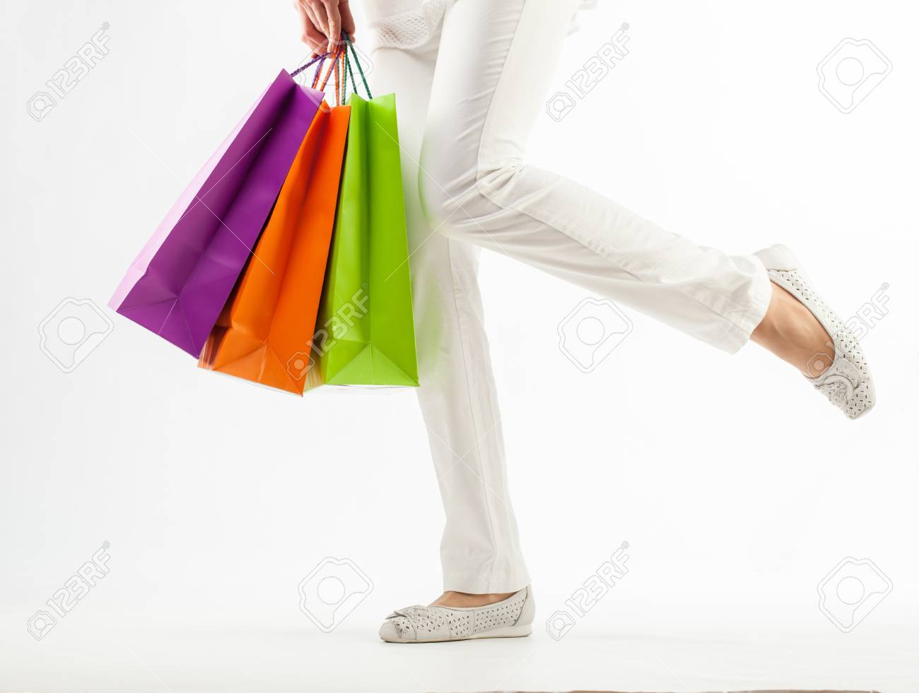 Girl holding multicolored shopping paper bags - closeup shot on white background Stock Photo - 16235111