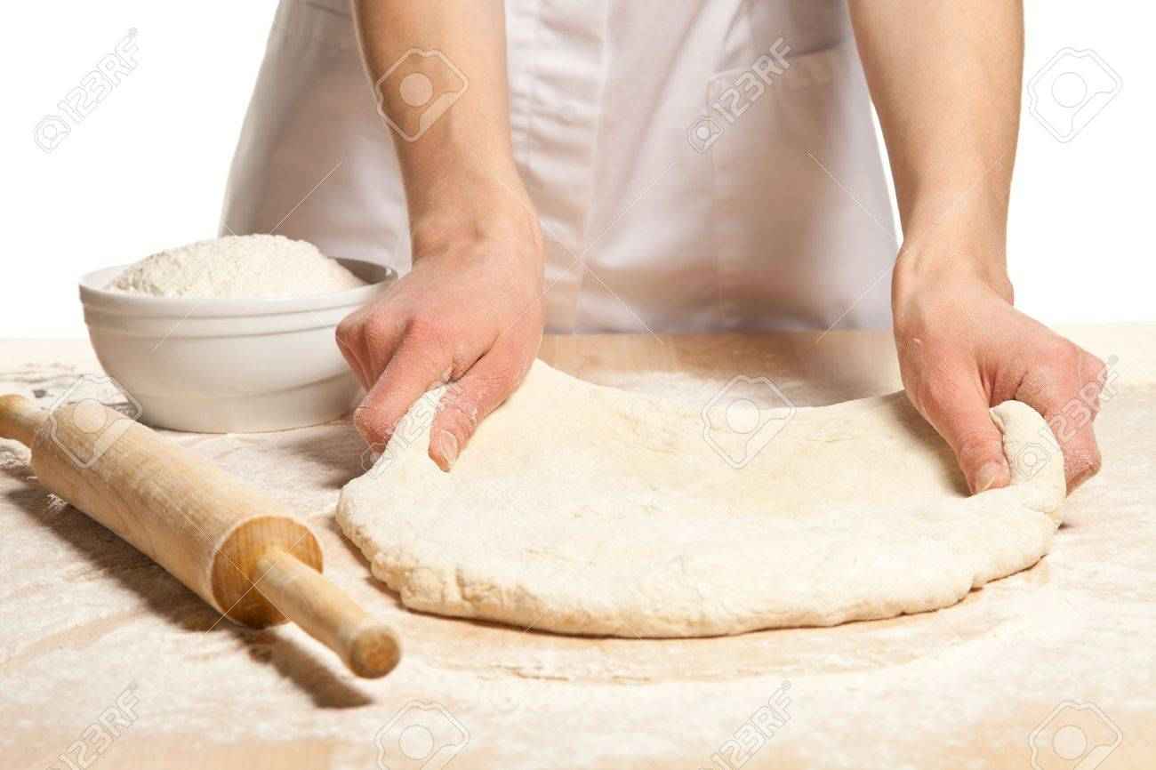 Hands stretching dough on wooden table; white background - 18157819
