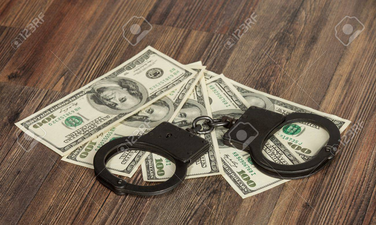 Handcuffs and money on the table Stock Photo - 19310777