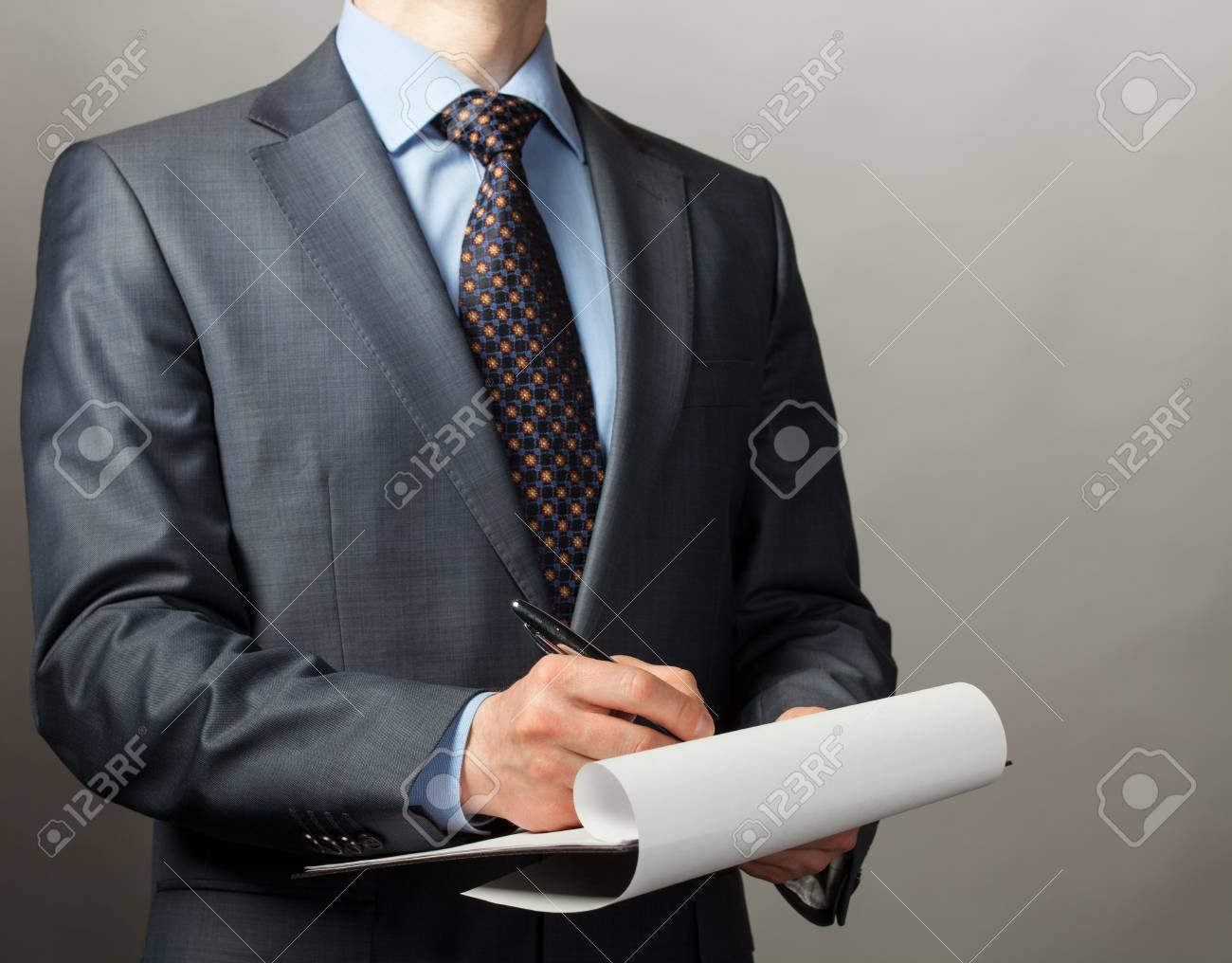 Businessman making notes on the paper, grey background - 19310674
