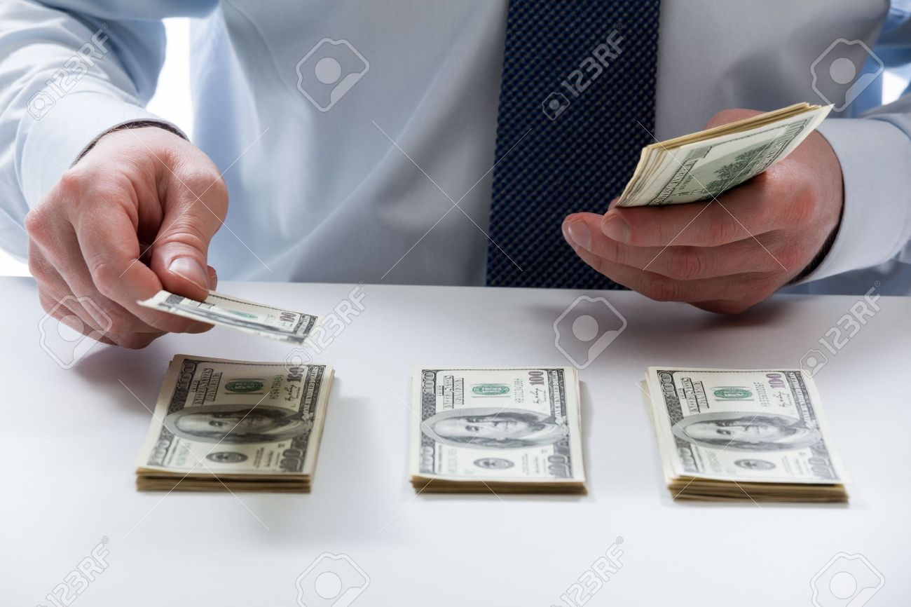 Bank teller's hands counting dollar banknotes on the table - 20935090