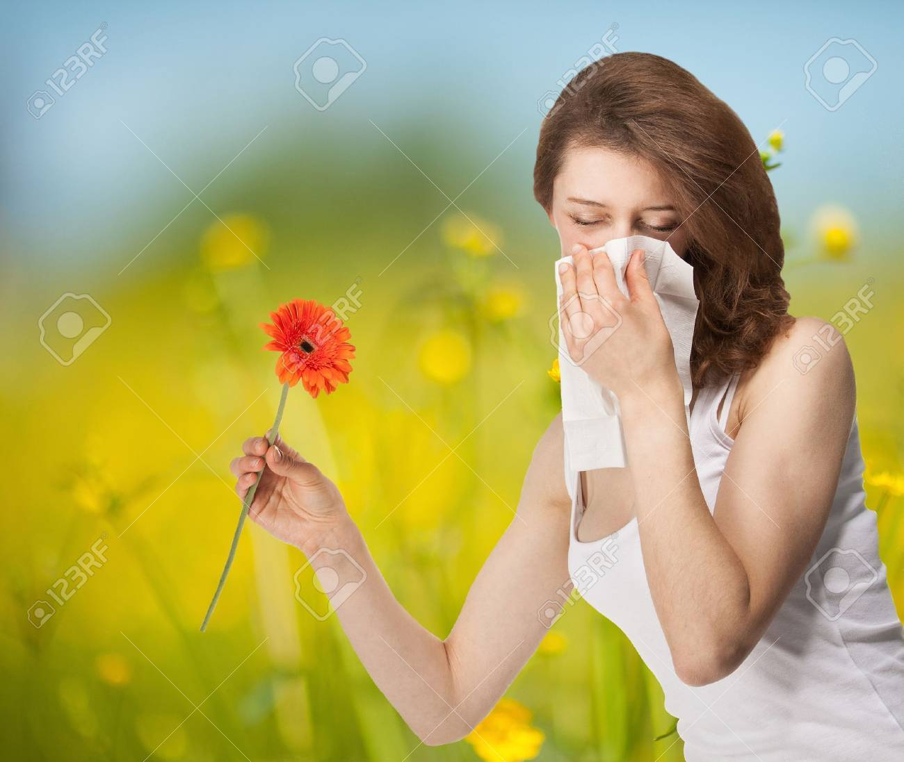 Young woman having allergy staying outdoors in a summer meadow with red herber - 21319073