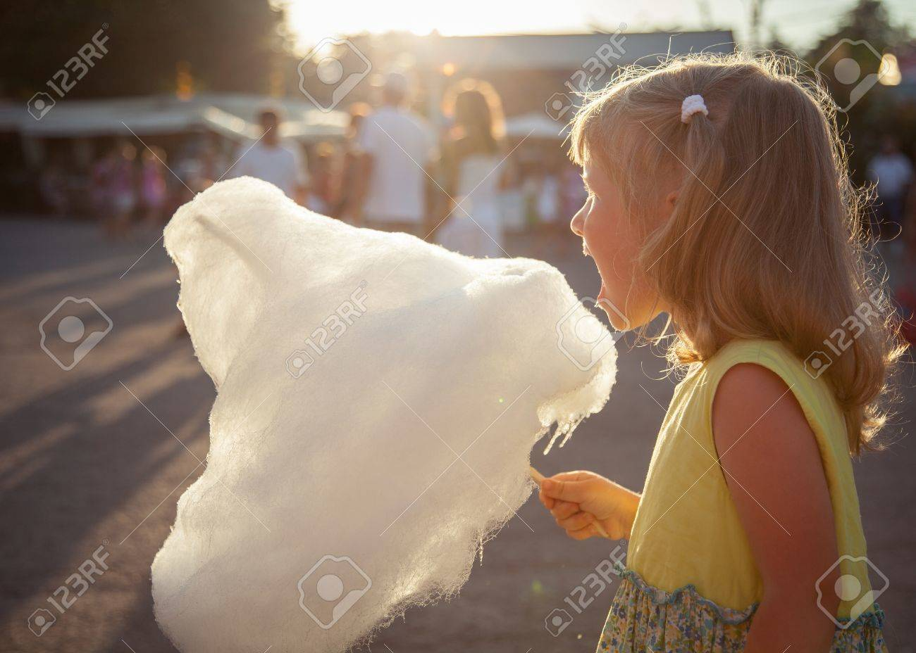 Charming little girl eating cotton candy - 21319447