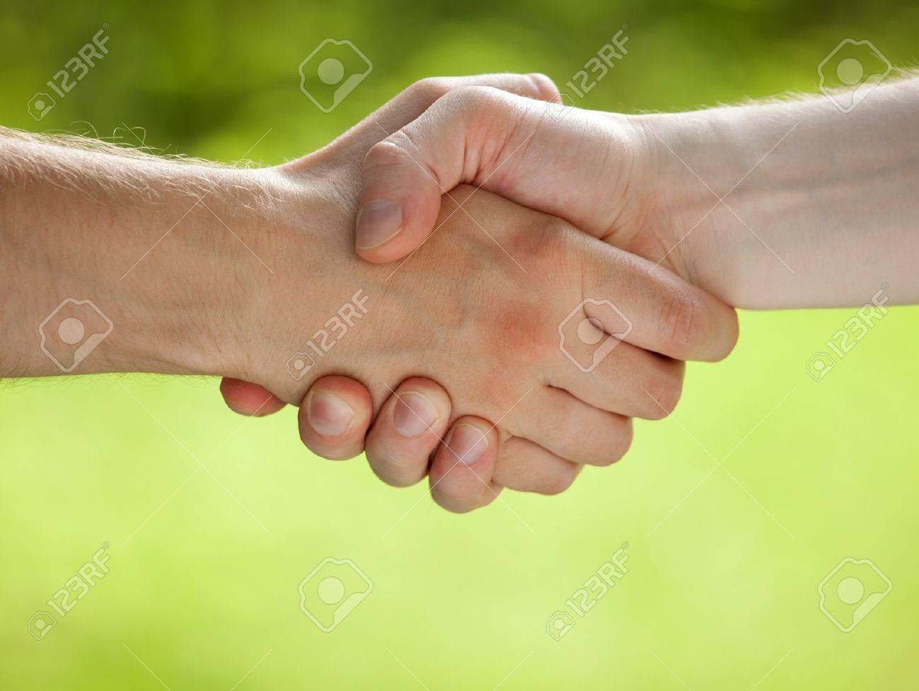 Handshake on light green eco background - 21320123