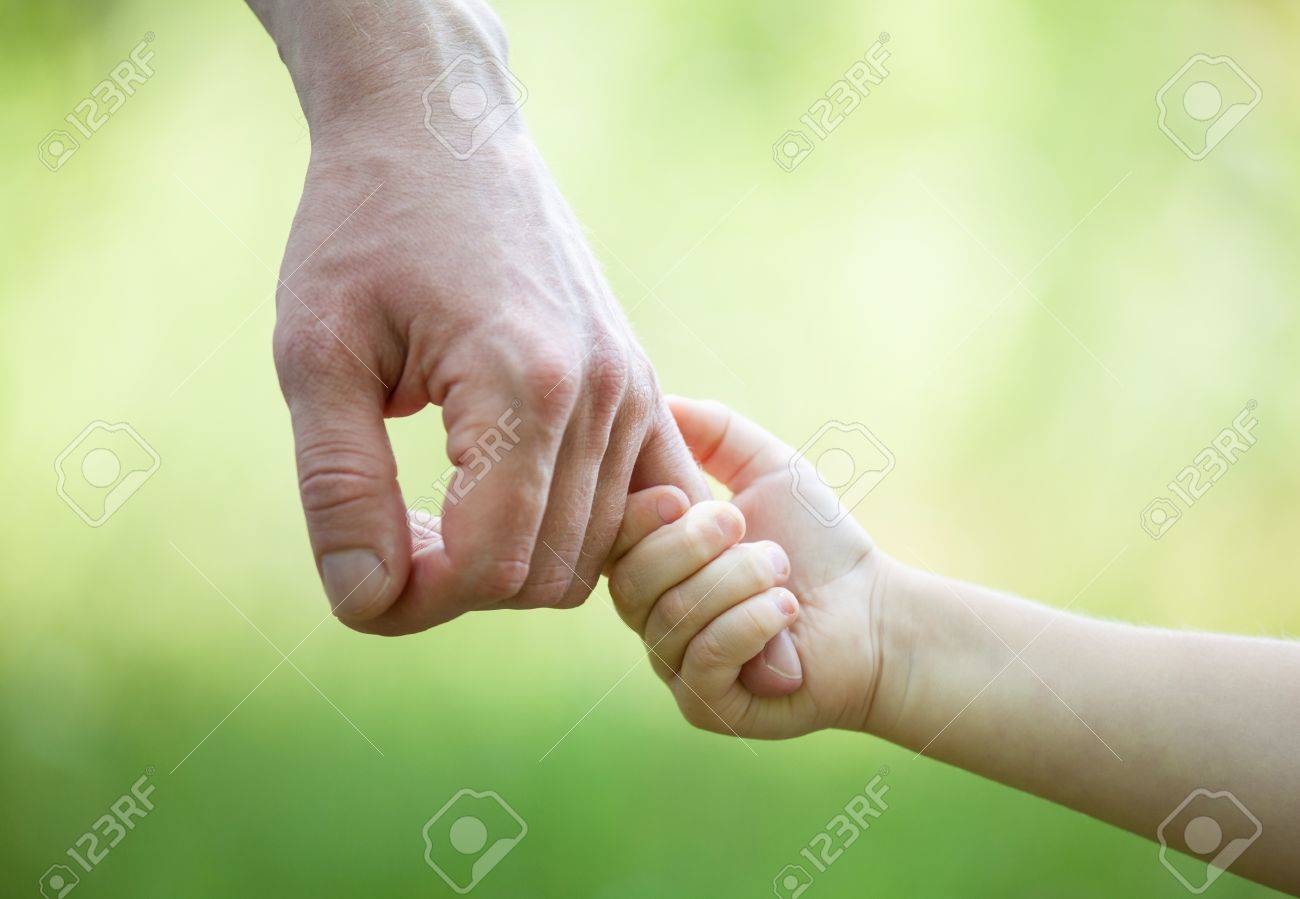 : Hands of man and child holding together on light green background - 21320151