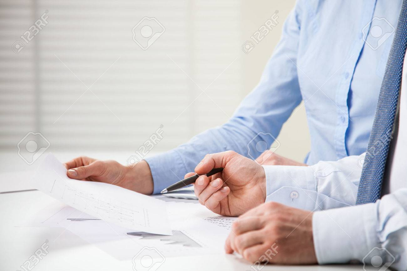 Business people discussing financial charts - closeup shot of hands over table - 31547653