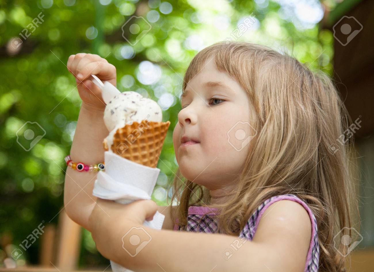 Pretty little girl eating an ice cream outdoors - 31547762