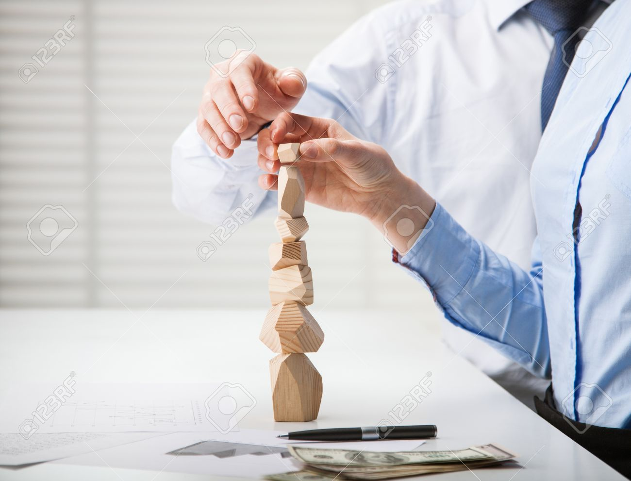 Business people building wooden tower (Japanese game tumi-ishi), illustrating concept of business success, cooperation, achievement and self-control - 31547763