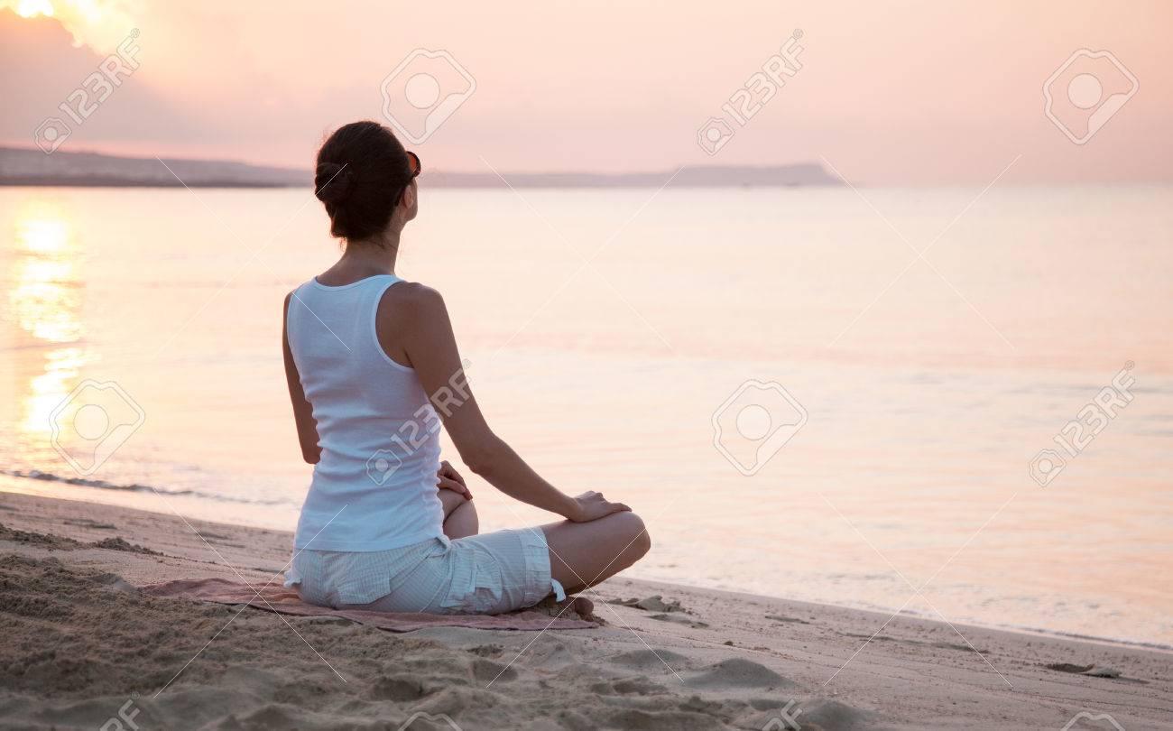 Young woman meditating on the sea coast at dawn - 41322296