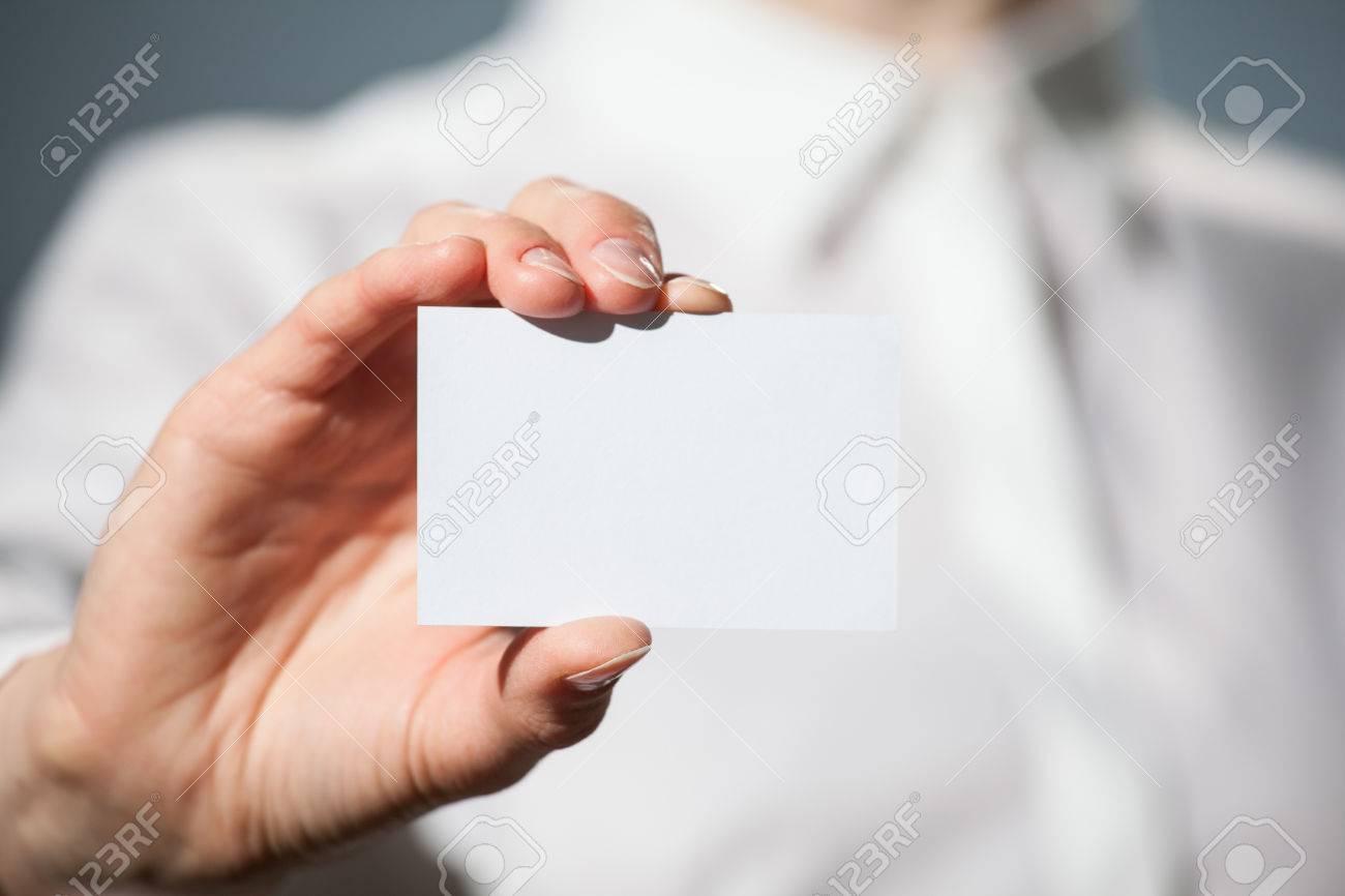 Businesswoman's hand showing business card on dark background - 44540360