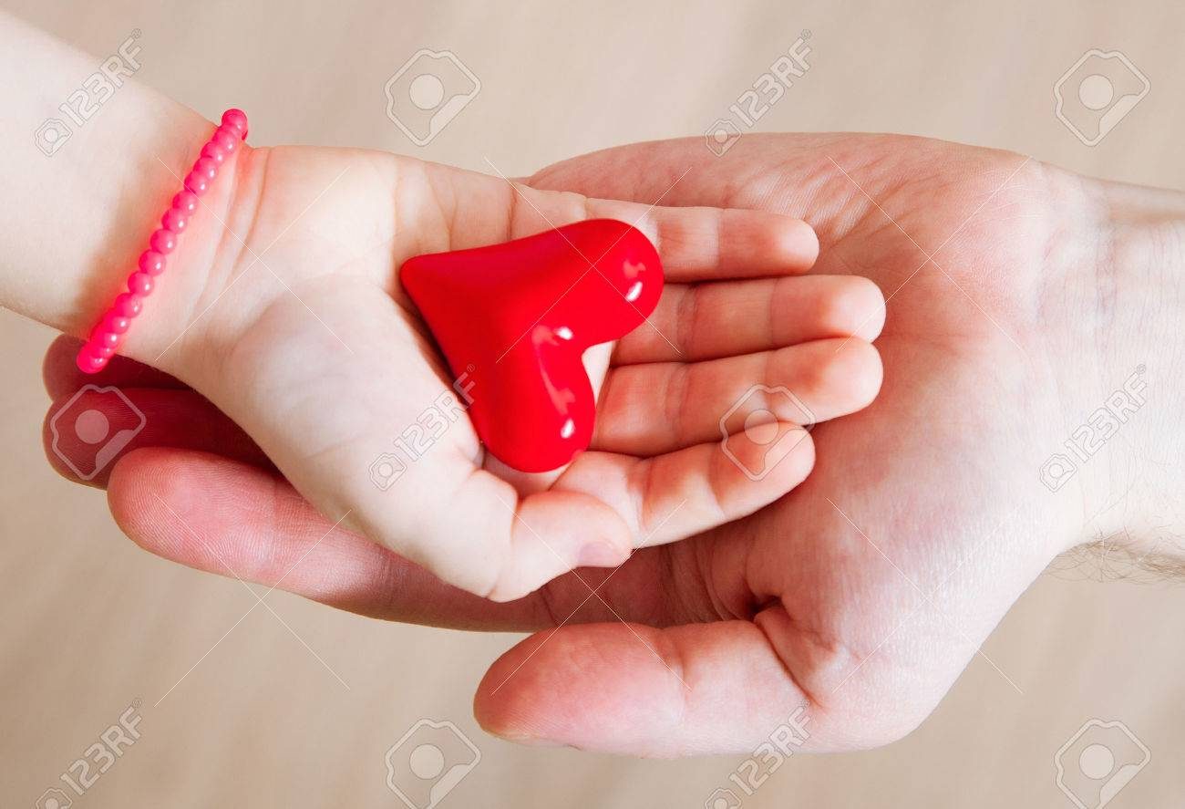 Daughter and her father holding a red heart in their hands, neutral background - 48050286