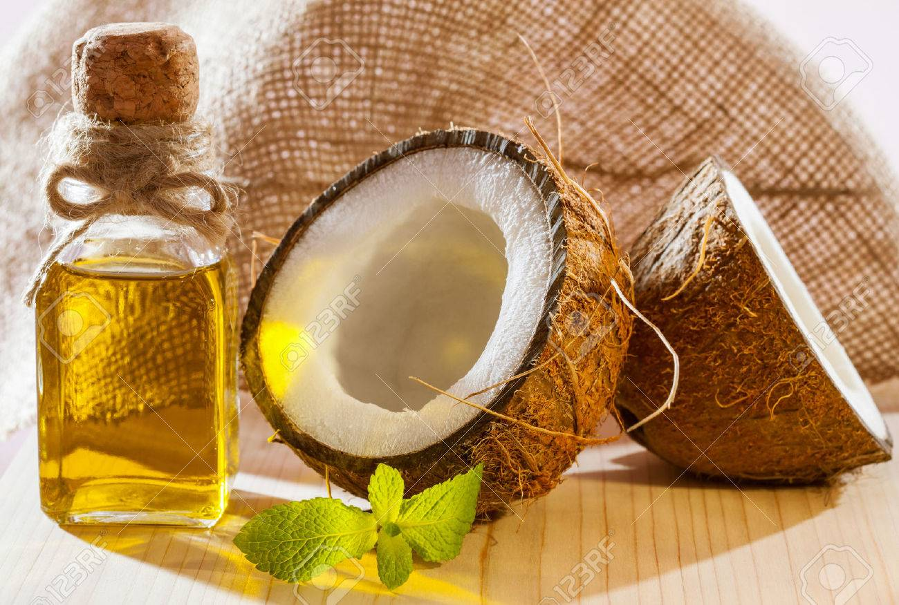 Fresh coconut, bottle of oil and mint leaf on wooden table - beautiful skincare and haircare composition - 52080461