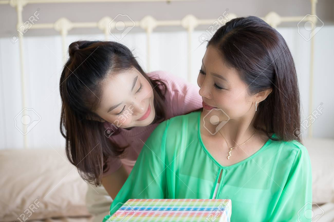 Happy Family Teen Daughter Giving Birthday Present To Mother At Home Stock Photo