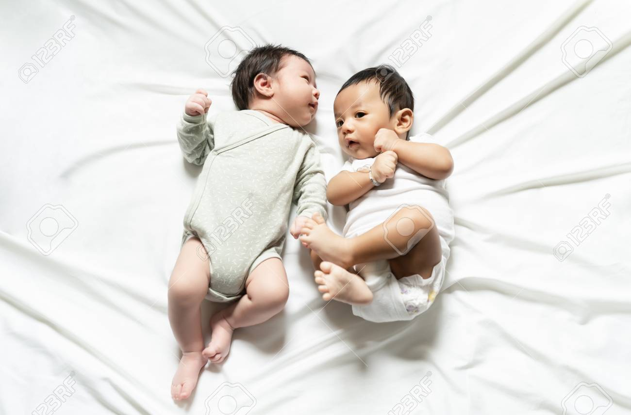 Two adorable twin babies smiling happily on the bed happy childhood family new