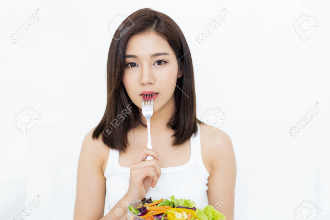 Portrait of young Asian woman eating healthy salad and pressing fork to her lips and looking at camera isolated on white white background - 112180732
