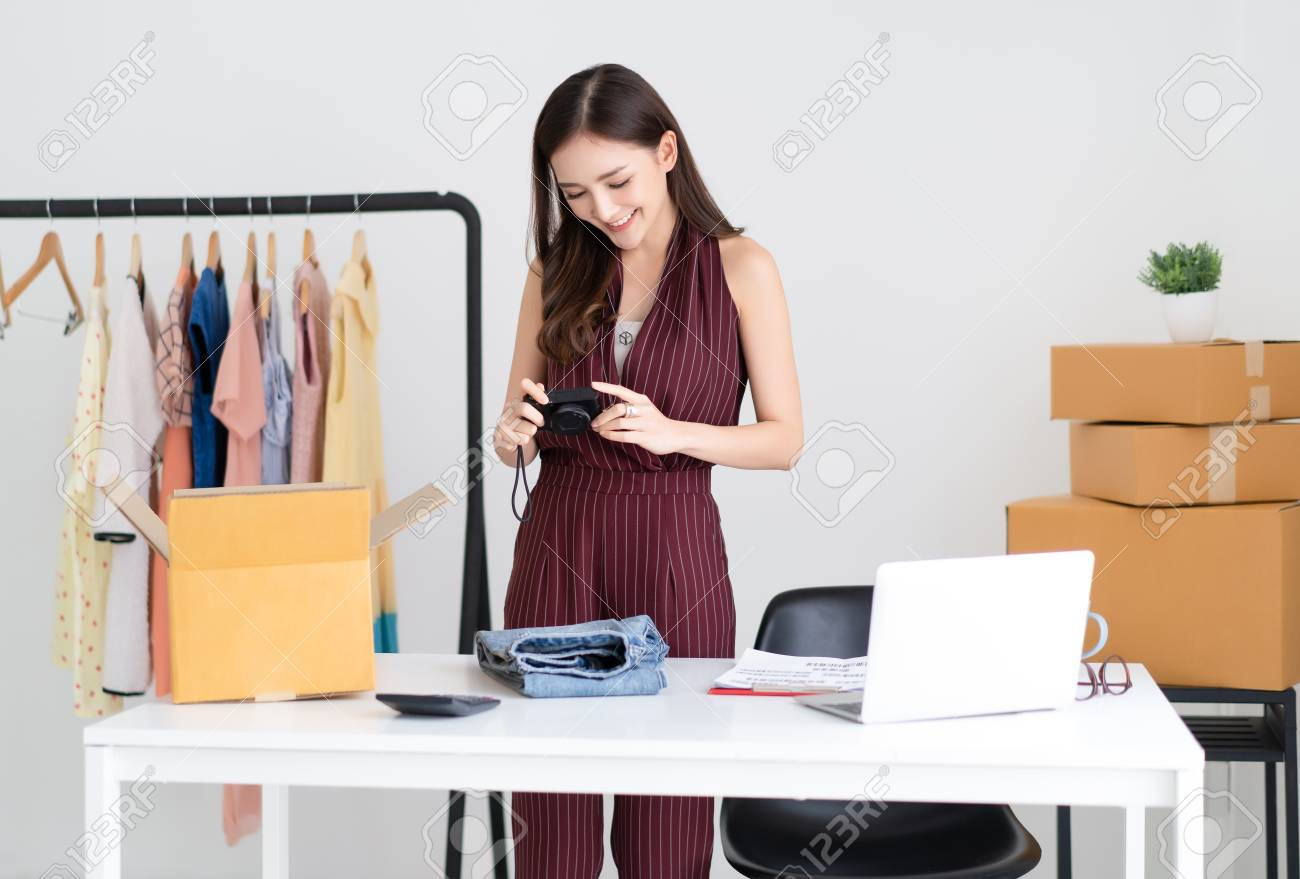 Young Asian casual woman working small business taking picture of product on digital camera for selling on website in home office. Startup Small business owner,Online selling, e-commerce, delivery, freelance working concept. - 118619597