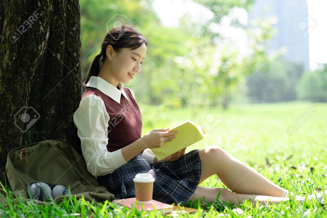 Portrait of beautiful smiling Asian woman sitting on green grass in park and relaxing while reading a book. - 123934572